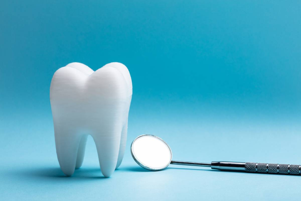 3D image of a tooth standing beside a dental tool.